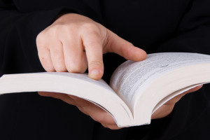 Young business woman in dark suit reading book and pointing line.